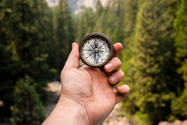 Man following his passion by looking at a compass.